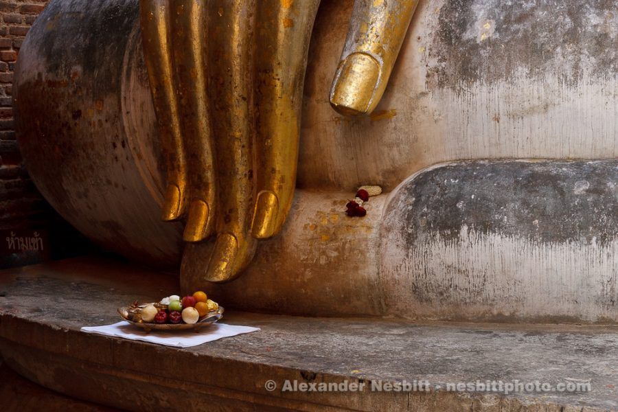 Gilded Buddha hand of giant Buddha statue with offering of fruit