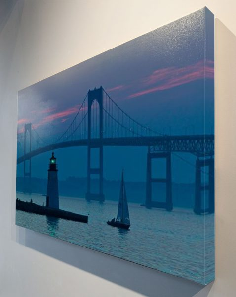 Blue dusk with bridge, green light and one sail boat