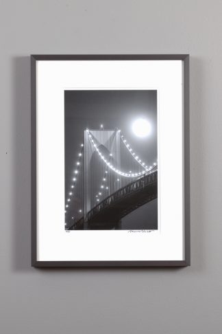 black and white image of the newport bridge under a full moon
