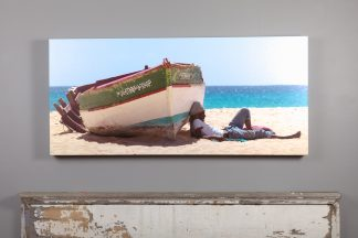 22x48 canvas print, man relaxes in shadow of old beached boat Sal, Cape Verde