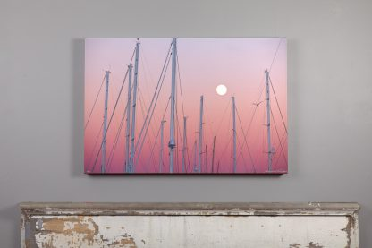 24x36 canvas print of a full moon over the shipyard hangs above a mantle