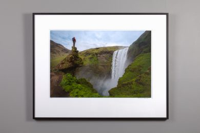 framed 16x24 image of hiker looking down on skogafoss waterfall in iceland