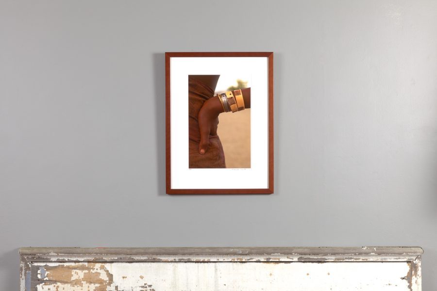 framed 11x14 image of a himba woman's arm resting on her hip, hanging above a mantle