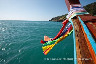 Long tail boat ride on the Andaman sea, Thailand. Colorful scarves