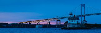 The Newport Bridge catches the last rays of sunset behind the Rose Island Light house