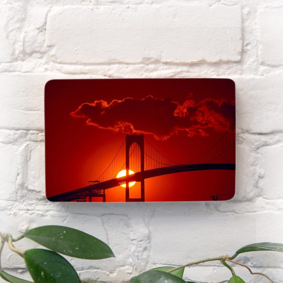 Setting sun centered behind tower of Newport Bridge